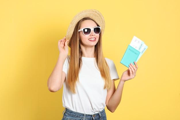 Красивая молодая улыбающаяся девушка держит билеты на поездку на отдых
