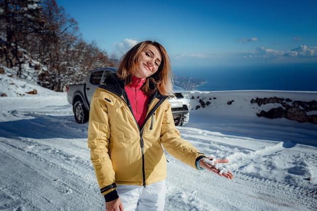彼女の冬の暖かい服を着た美しい若い笑顔の女の子。自然の美しい冬の山の風景を背景に、海の景色を望む山の美しい観測点に