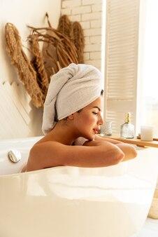 バスルームの浴槽に横たわってリラックスして美しい若い笑顔の女の子。彼女の頭に白いタオル。自宅でのケアと美容のコンセプト
