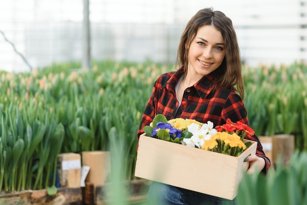 아름 다운 젊은 웃는 소녀, 온실에서 꽃과 노동자. 복사 공간, 튤립 정원