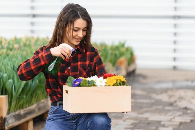 美しい若い笑顔の女の子、温室の花を持つ労働者。