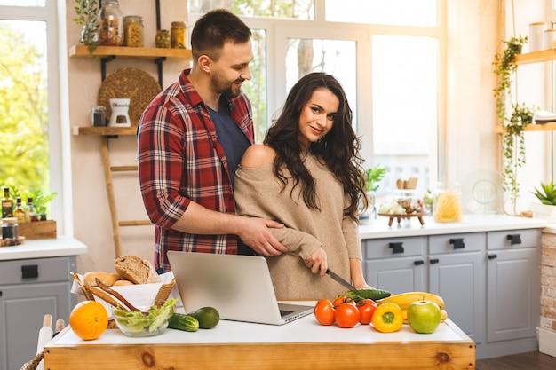 Красивая молодая усмехаясь счастливая пара говорит и усмехается пока варящ здоровую еду с компьтер-книжкой в кухне дома.