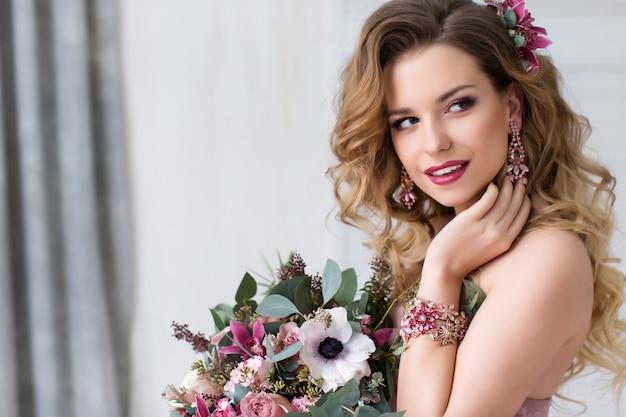 밝은 꽃과 함께 아름 다운 젊은 웃는 모델. 아름다움과 패션