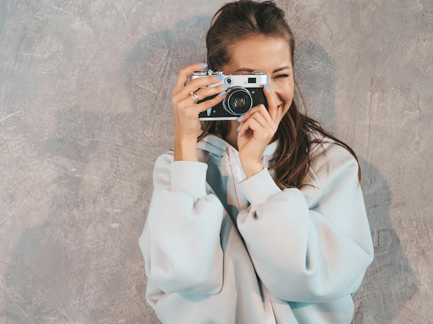 Beautiful young smiling photographer girl taking photos using her retro camera. woman making pictures. model dressed in casual summer hoodie. posing in studio near gray wall