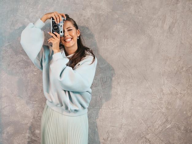 Beautiful young smiling photographer girl taking photos using her retro camera.