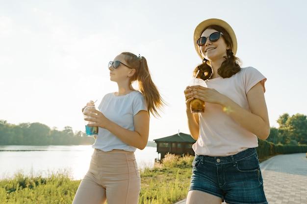 Beautiful young smiling teen girls walking on nature