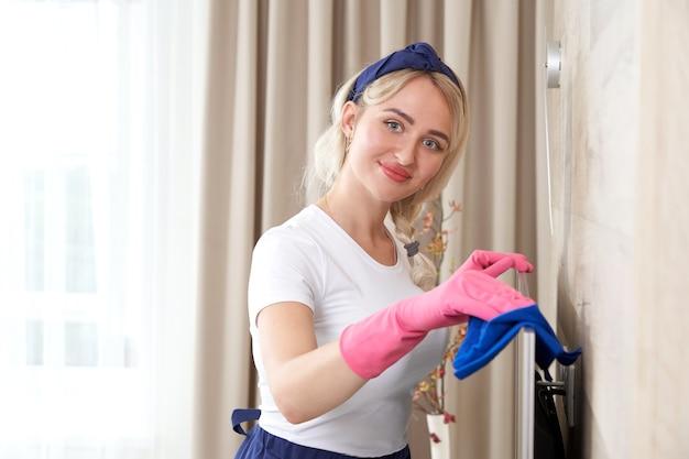 マイクロファイバーの布で家を掃除する美しい若い笑顔の女性。自宅でクレンザーでテレビを掃除している女性、クローズアップ。自宅のリビングルームの家具を掃除する若い幸せな女性