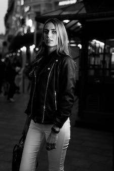 저녁 도시에서 아름 다운 젊은 웃는 여자