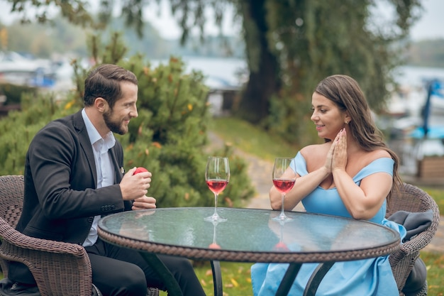 Beautiful young smiling woman and man with gift sitting at table opposite each other with wineglass outdoors