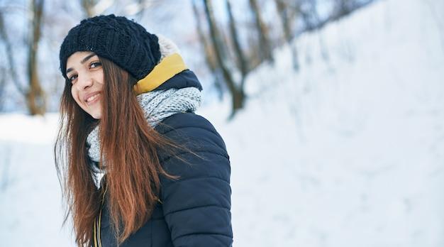 冬の外で美しい若い笑顔の女性