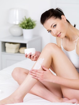 Beautiful young smiling woman sitting on a bed and applying cream on her attractive legs - vertical