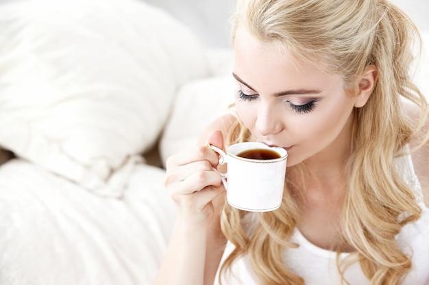 Красивая молодая улыбающаяся женщина, сидящая на белой кровати, пьет чашку кофе