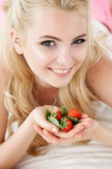 야생 딸기 딸기의 무리를 들고 흰색 침대에 앉아 아름 다운 젊은 웃는 여자