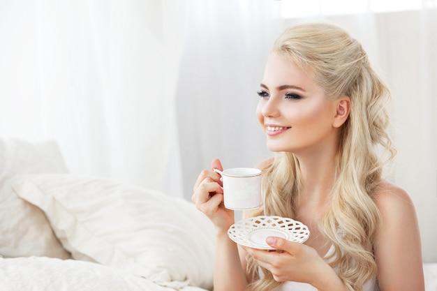 白いベッドに座って、コーヒーを持って美しい若い笑顔の女性。朝起きます。白い髪の色、明るい色調で撮影。美女の顔