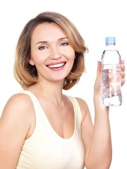 白い壁に水のボトルを持つ美しい若い笑顔の女性。