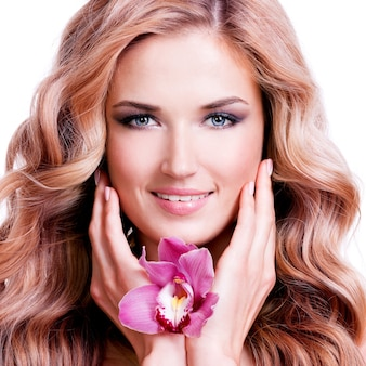 顔の近くに花を持つ美しい若い笑顔の女性。美容トリートメントのコンセプト。白い壁の上の肖像画。