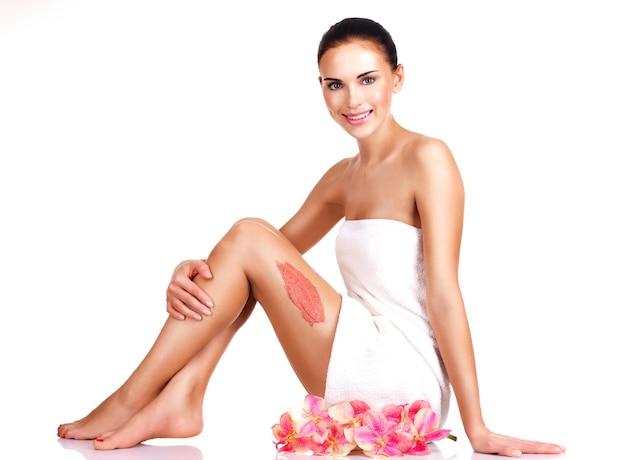 Bella giovane donna sorridente con i fiori utilizzando uno scrub.