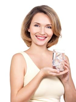 Bella giovane donna sorridente con un bicchiere d'acqua su un muro bianco