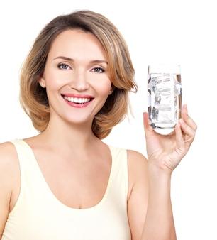 Bella giovane donna sorridente con un bicchiere d'acqua su bianco
