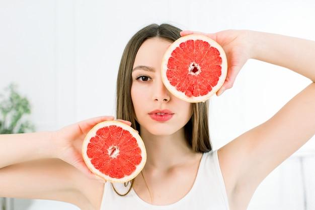 白で隔離されるグレープフルーツの部分を保持している長い髪、完璧な肌、完璧なメイクで美しい若い笑顔の女性