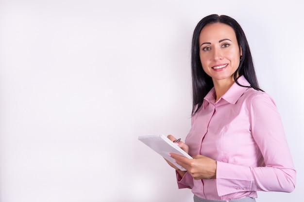 メモ帳と美しい若い笑顔の女性