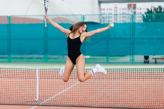 테니스 코트에서 바디 슈트를 입은 아름다운 젊은 스포츠 여성
