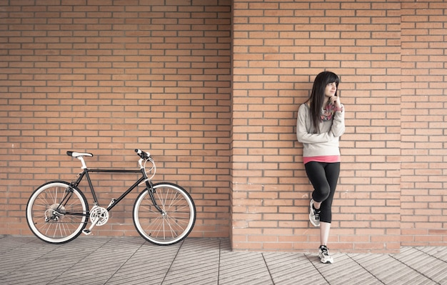 Beautiful young sportive woman posing with custom fixie bike over a orange brick wall on the background