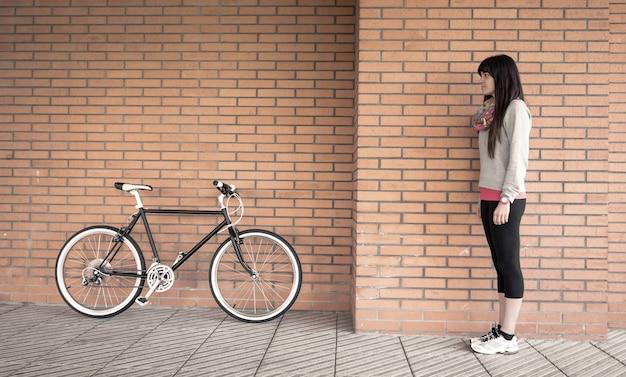 배경에 주황색 벽돌 벽 위에 맞춤형 픽시 자전거와 함께 포즈를 취하는 아름다운 젊은 낚시를 좋아하는 여성