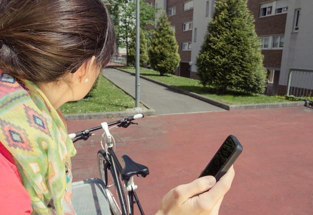 화창한 여름날 공원 벤치에 앉아 스마트폰을 보고 있는 맞춤형 픽시 자전거를 가진 아름다운 젊은 여성. 부드럽고 따뜻한 음색.
