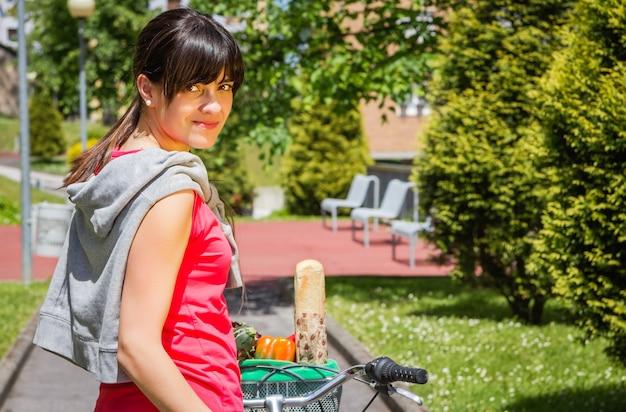 화창한 여름날 바구니 자전거에 식료품을 든 아름다운 젊은 여성