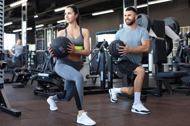 美しい若いスポーツカップルがジムで薬のボールを使って運動しています。