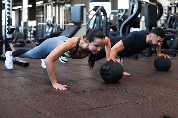 Красивая молодая спортивная пара работает с мячом в тренажерном зале.