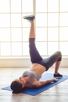 Beautiful young sports lady is doing yoga in fitness hall