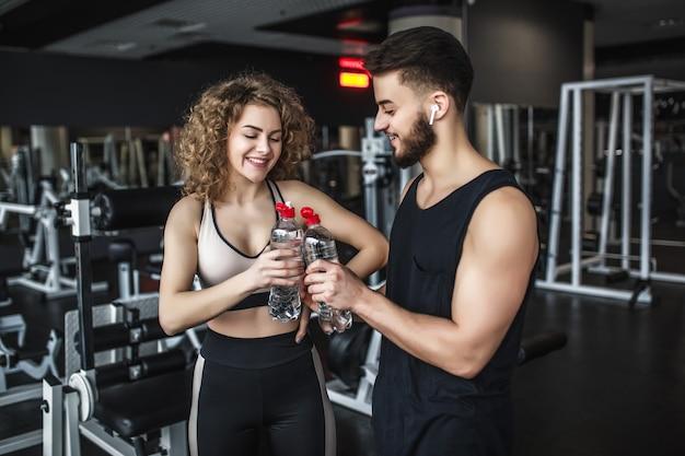 Bellissimi giovani sportivi tengono in mano bottiglie d'acqua, sorridono durante la pausa