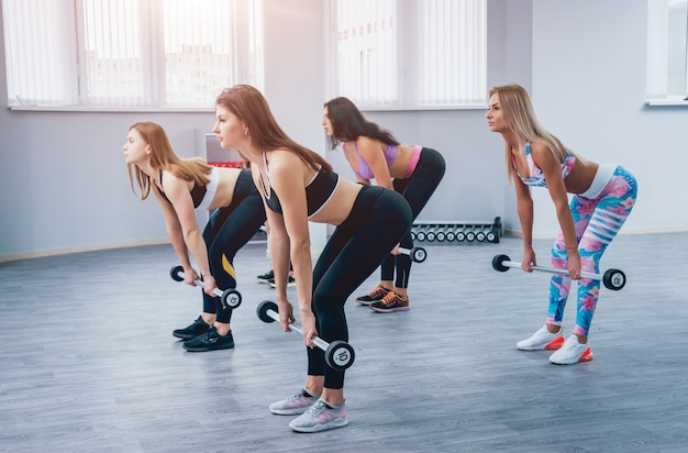 Красивые молодые спортивные женщины, накачивание мышц с гантелями в тренажерном зале.