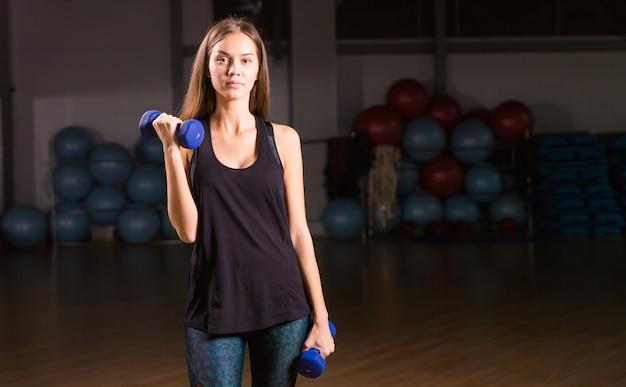 체육관에서 아령으로 운동을 하 고 아름 다운 젊은 sportswoman.