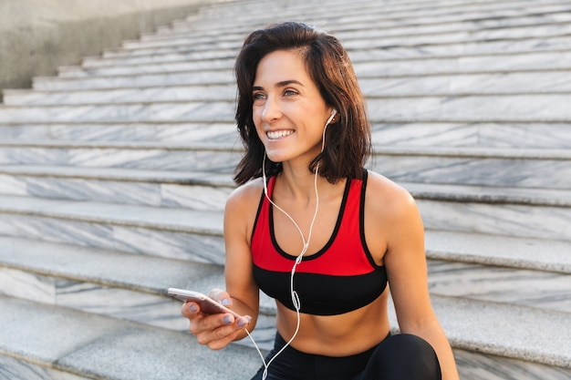 Красивая молодая спортсменка держит мобильный телефон, слушает музыку в наушниках, пьет воду