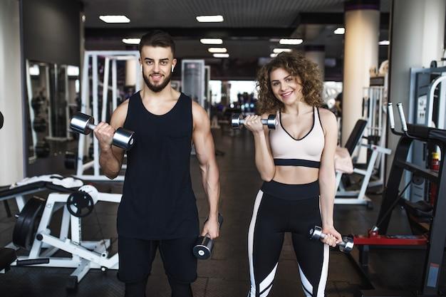 トレーニング中にジムで筋肉とトレーニングを示す美しい若いスポーティなカップル