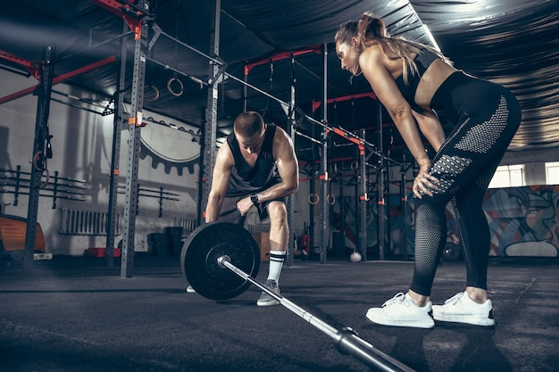 Beautiful young sporty couple training workout in gym together
