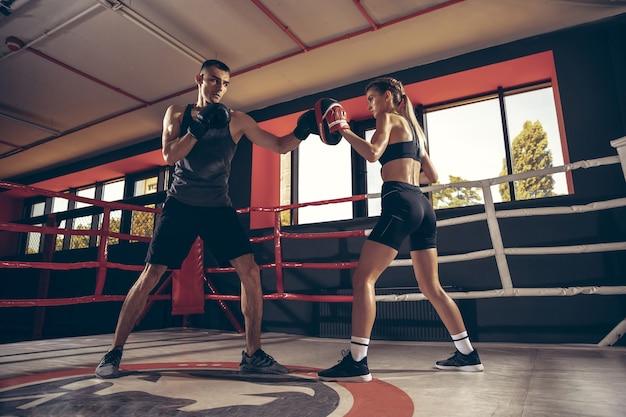一緒にジムで美しい若いスポーティなカップルのトレーニングトレーニング