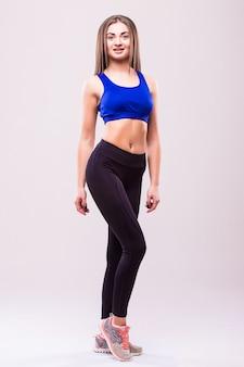白い背景に対して隔離の美しい若いスポーティな筋肉の女性