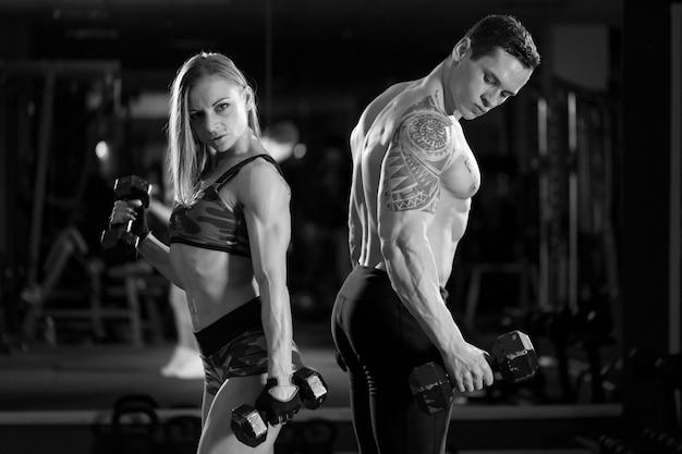 ジムで筋肉とトレーニングを示す美しい若いスポーティなセクシーなカップル。黒と白