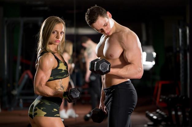 Красивые молодые sporty сексуальные пары показывая мышцу и разминку в спортзале