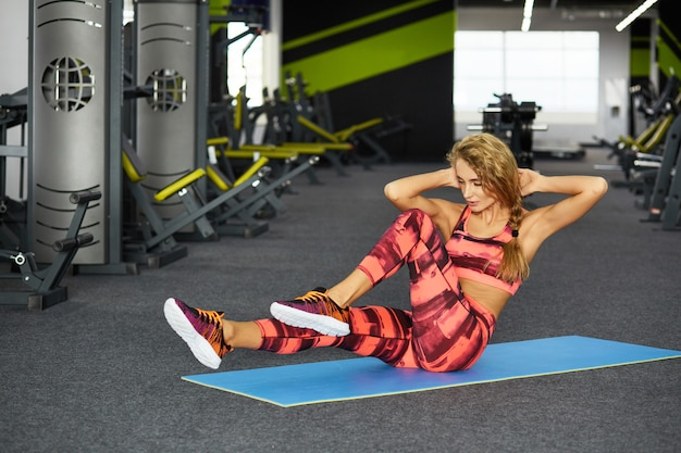 Beautiful young sporty woman doing sport exercises in gym. fitness.