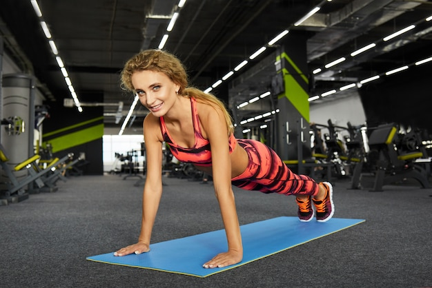 Beautiful young sporty woman doing sport exercises in gym