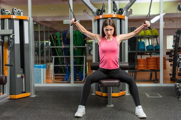 피트니스 센터에서 체육관 방에서 행 기계에 대한 교육 아름다운 젊은 스포티 한 여자