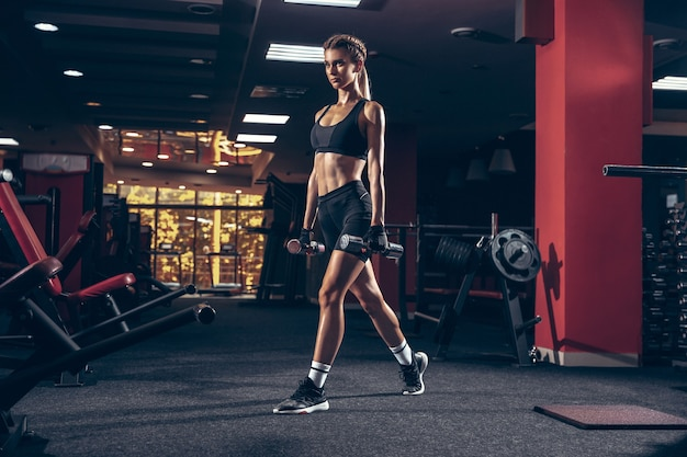 Beautiful young sporty woman training workout in gym