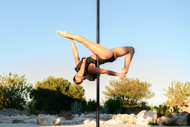 Beautiful young strong woman making a pose on a pole.