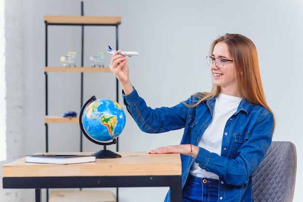 Beautiful young student girl having fun while exploring the globe with model of airplane. studying geography with globe.