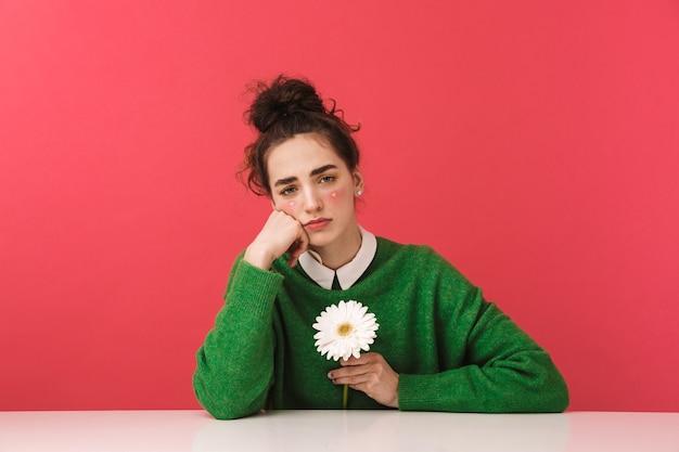 Красивая молодая студентка девушка сидит за столом в изоляции, держа цветок ромашки